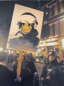 2003:5:1 - SA - UK - London - Smiley cooper on placard - Wall and piece p228